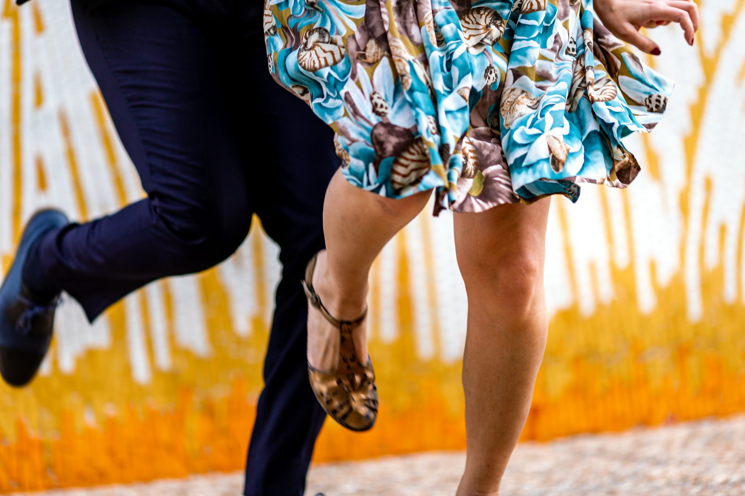 Two people dancing from the waist down, with vintage clothes and shoes and a bright summery background