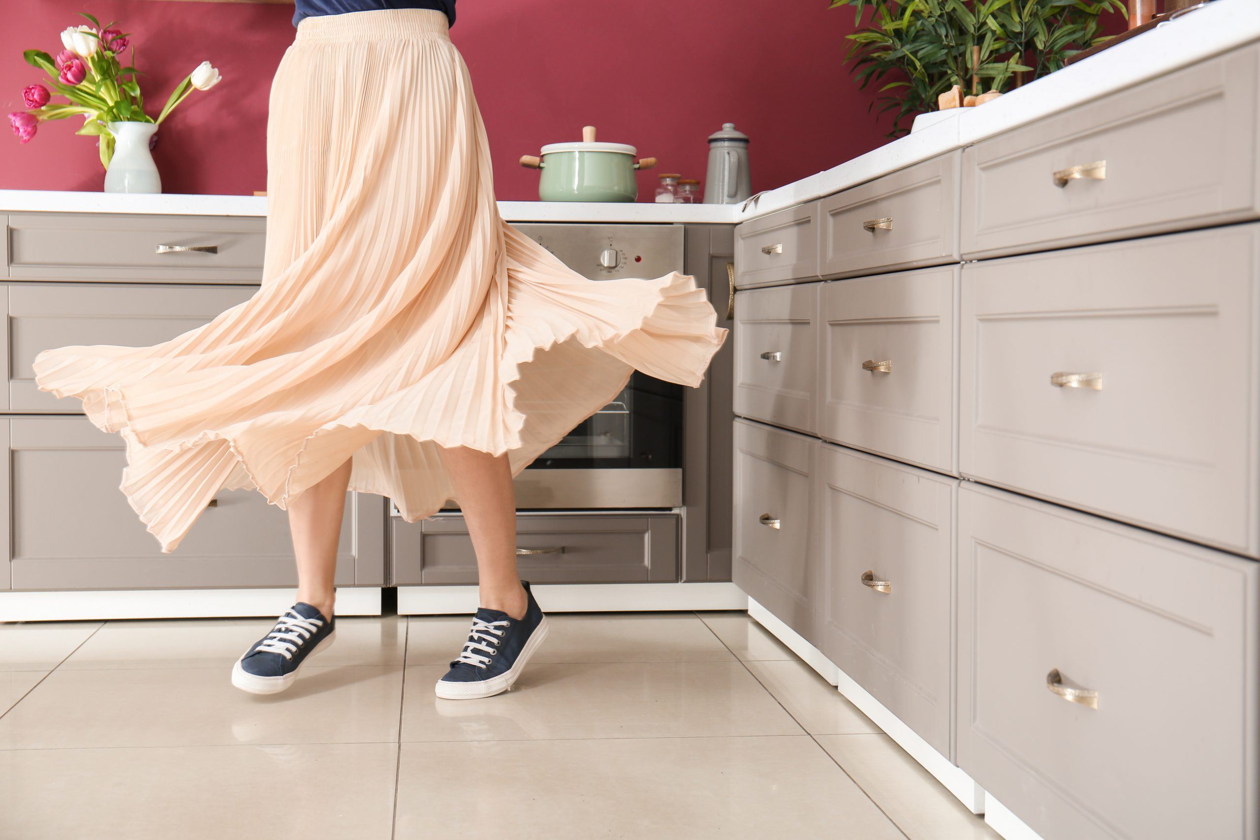 Person in a long skirt and sneakers dances in the kitchen
